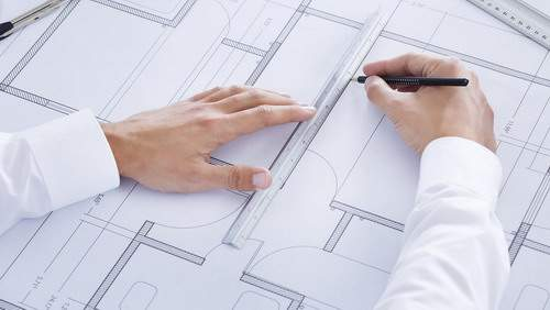 Close-up Of Male Architect Working On Blueprint At Desk