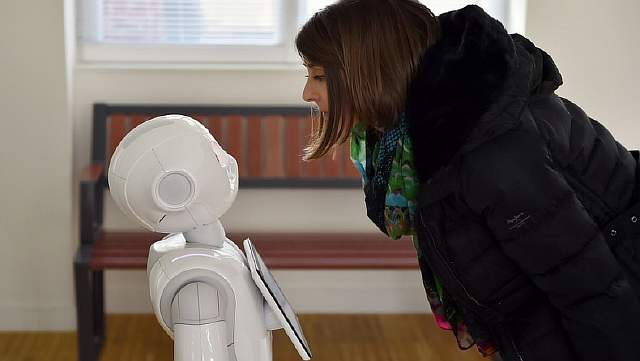 Женщина взаимодействует с роботом, предоставляющим информацию пассажирам французской железнодорожной компании SNCF