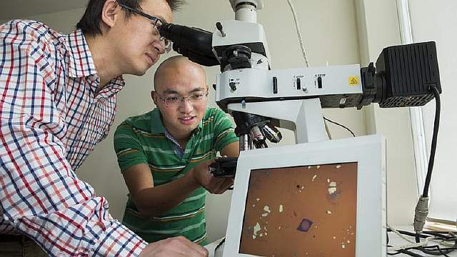 Доктор Ларри Лу наблюдает линзы в микроскоп