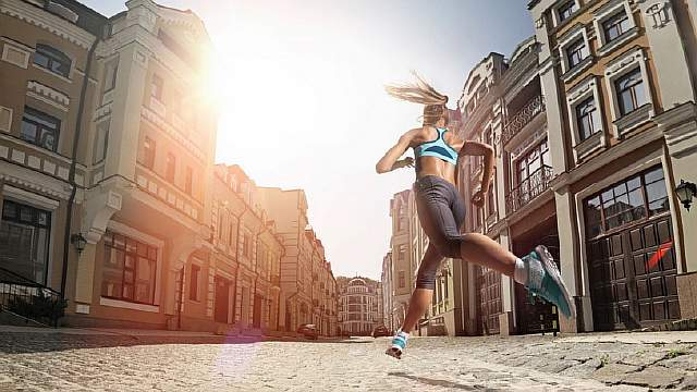 woman-running-down-cobblestone-city-streets_h